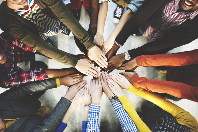 Many people with their hands clasped in a circle