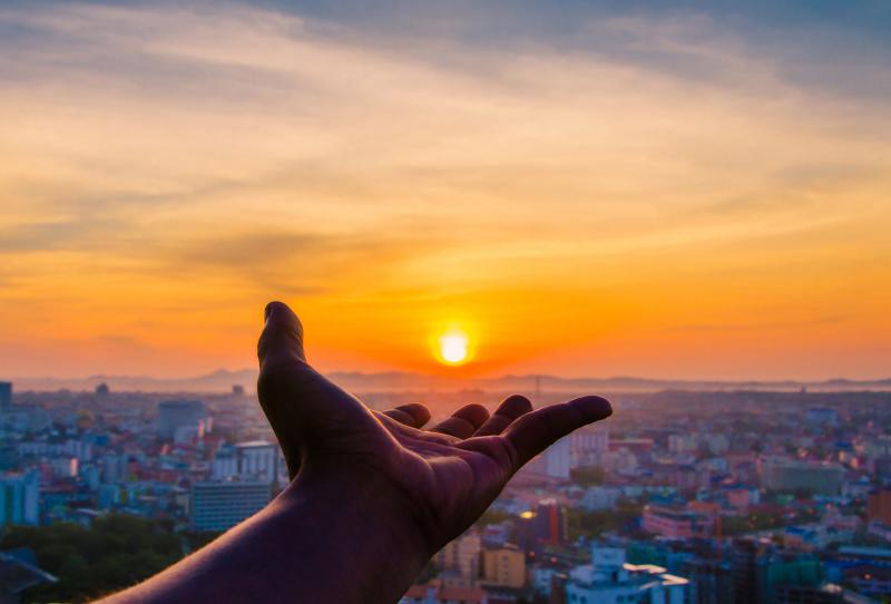 Hand extended towards the setting sun
