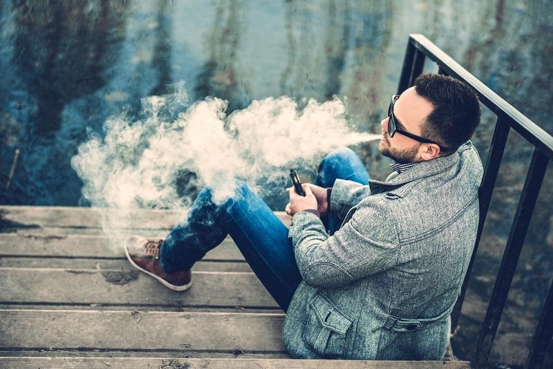 Man sitting by water smoking Cannabis vape cartridge
